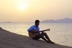日出的吉他弹奏者在海滩 免版税库存图片