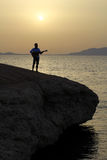 日出的吉他弹奏者在海滩 免版税图库摄影