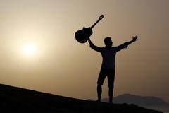 日出的吉他弹奏者在海滩 库存照片