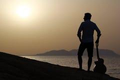 日出的吉他弹奏者在海滩 免版税库存照片