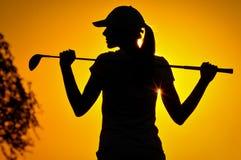 日出的女性高尔夫球运动员 库存照片
