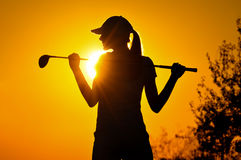 日出的女性高尔夫球运动员 免版税库存照片