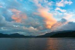 日出的Mountain湖与在距离的渔船 图库摄影