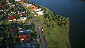 日出赛船会在湖和Parkland英属黄金海岸草玩耍区域议院庄园浇灌在湖的Coomera河旁边, 免版税库存照片