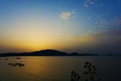 日出从山的后面向海 库存图片