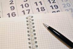 日历、笔记本和笔 免版税库存照片