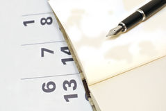 日历、笔记本空白页和黑笔 免版税库存照片