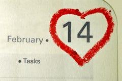 日历与红色手书面心脏聚焦o的笔记本页 免版税图库摄影