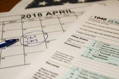 日历和形成1040所得税形式归档的2017年显示的税天是2018年4月17日 免版税库存图片