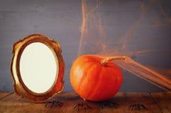 日历概念日期冷面万圣节愉快的藏品微型收割机说大镰刀身分 在空白的照片框架旁边的南瓜 图库摄影