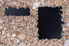 日历,菜单和建于小海石头和壳在黑背景 填写的空的领域,笔记与 库存图片