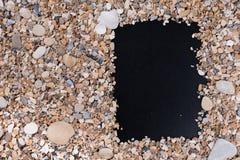 日历,菜单和建于小海石头和壳在黑背景 填写的空的领域,笔记与 免版税库存图片
