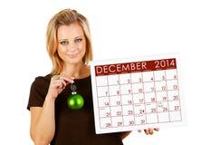 2014日历:拿着12月圣诞节装饰品 图库摄影