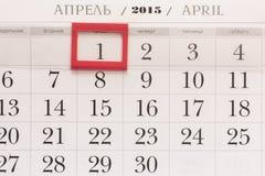 2015年日历 与红旗的4月日历在被构筑的日期 免版税库存照片