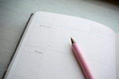 日历/天计划者日志与笔在开放页 库存图片