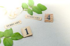日历2月14日,与玫瑰色花的木在沙子背景 免版税图库摄影