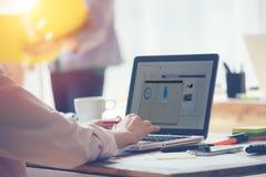 日在办公室 膝上型计算机和文书工作在桌上 合作谈论工作的想法和的经理与在膝上型计算机的项目 库存图片