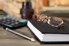 日志、玻璃和一支简单的黑铅笔在桌面上说谎 特写镜头 选择聚焦 库存图片