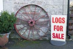 日志木头待售标志在生物量燃烧器的农厂商店 图库摄影