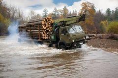 日志的运输的重型卡车在河移动浅滩 免版税库存图片