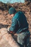 日志记录器砍灰树从锯的到木头,并且为冬天期间做准备 库存照片