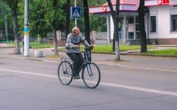 日托米尔,乌克兰- 2015年9月05日:周期乘驾的老人在乡下 库存照片