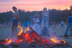 日托米尔,乌克兰- 2016年7月12日:庆祝在晚上的人们在海滩在火附近 免版税库存图片