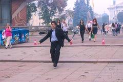 日托米尔,乌克兰- 2015年10月03日:有他的书包的愉快的男小学生在他的跑在街道的肩膀 免版税库存照片