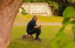 日托米尔,乌克兰- 2015年9月03日:老人用棍子坐树桩户外 图库摄影