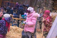 日托米尔,乌克兰- 2016年11月19日:获得滑稽的矮小的愉快的女孩与干草的乐趣在农场 免版税库存照片