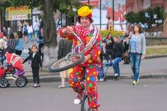 日托米尔,乌克兰- 2015年9月05日:跳在单轮脚踏车的小丑在街道 图库摄影