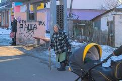 日托米尔,乌克兰- 2016年2月19日:公共汽车站的老妇人与标志弗拉基米尔・普京去远离乌克兰 免版税图库摄影