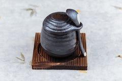 日本乳蛋糕布丁火炬了点燃在木板材的黑陶瓷杯子服务的上面的焦糖有盒盖和匙子的在washi 库存照片