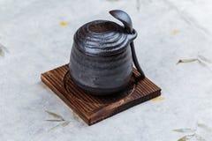 日本乳蛋糕布丁火炬了点燃在木板材的黑陶瓷杯子服务的上面的焦糖有盒盖和匙子的在washi 库存图片