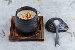 日本乳蛋糕布丁火炬了点燃在木板材的黑陶瓷杯子服务的上面的焦糖有盒盖和匙子的在washi 免版税库存图片