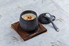 日本乳蛋糕布丁火炬了点燃在木板材的黑陶瓷杯子服务的上面的焦糖有盒盖和匙子的在washi 免版税图库摄影