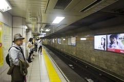 日本人和外国人旅客等待的地铁去t 免版税图库摄影