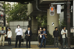 日本人和旅客外国人等待的交通标志为 库存照片