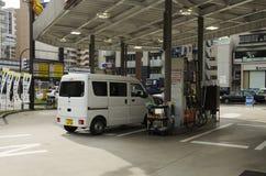 日本人推进搬运车去填装在加油站的油在嘘 库存图片