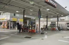 日本人推进汽车去填装在加油站的油在嘘 免版税库存图片