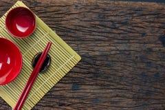 日本厨具套红色筷子、碗和杯子在竹席子和木桌背景 免版税图库摄影