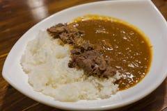 日本咖喱用米冠上用牛肉和葱在调味的一个温和地甜调味汁煨了 图库摄影