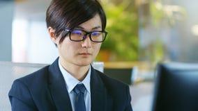 日本商人戴着眼镜的画象,坐在 库存图片
