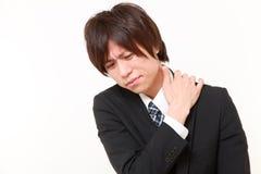 年轻日本商人遭受脖子疼痛 免版税库存照片