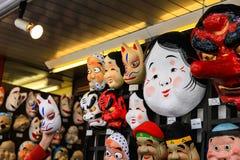 日本在墙壁上的面具吊 库存照片