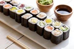 日本在白色木桌上的食物微型maki寿司盛肉盘 免版税库存照片