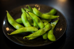 日本大豆当在黑盘的开胃菜食物 免版税库存照片