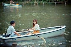 日本夫妇在公园用浆划一条小船 库存照片