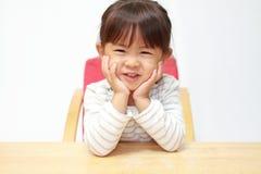 日本女孩在她的手上的休息她的下巴 库存图片