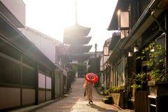 日本女孩在有红色伞的Yukata在老镇京都 库存照片